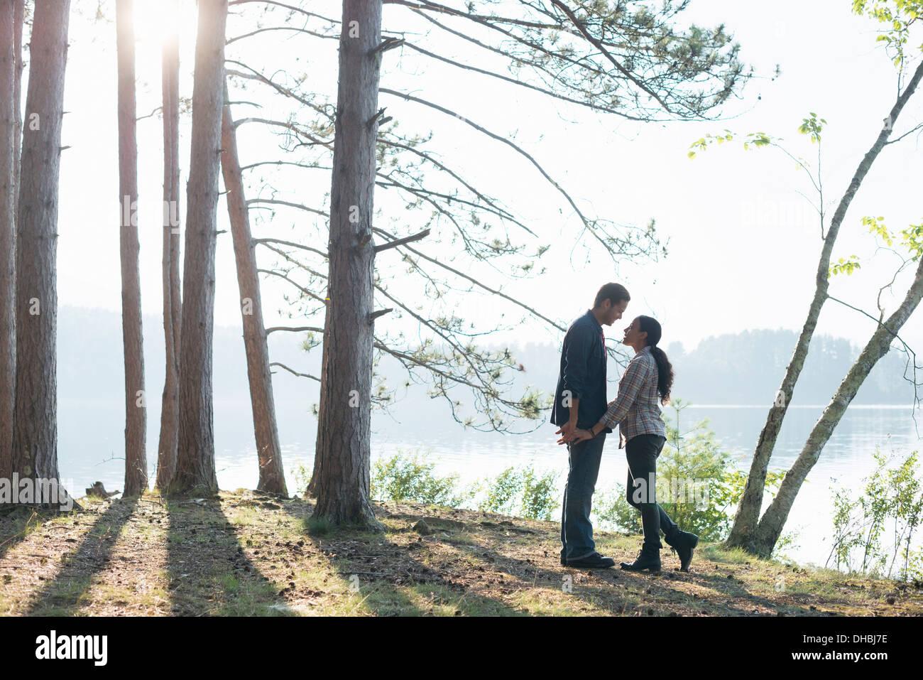 A la orilla del lago. Una pareja caminando en la sombra de los pinos en verano. Imagen De Stock