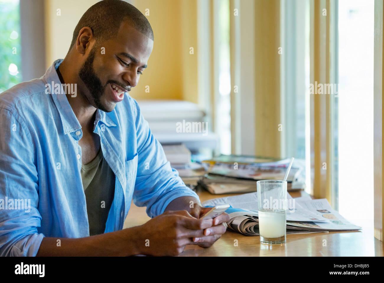 Un hombre sentado solo en un café, con su teléfono inteligente. Imagen De Stock