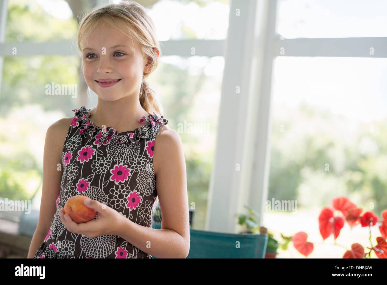 Una joven en un vestido floral sosteniendo un melocotón fruta. Imagen De Stock