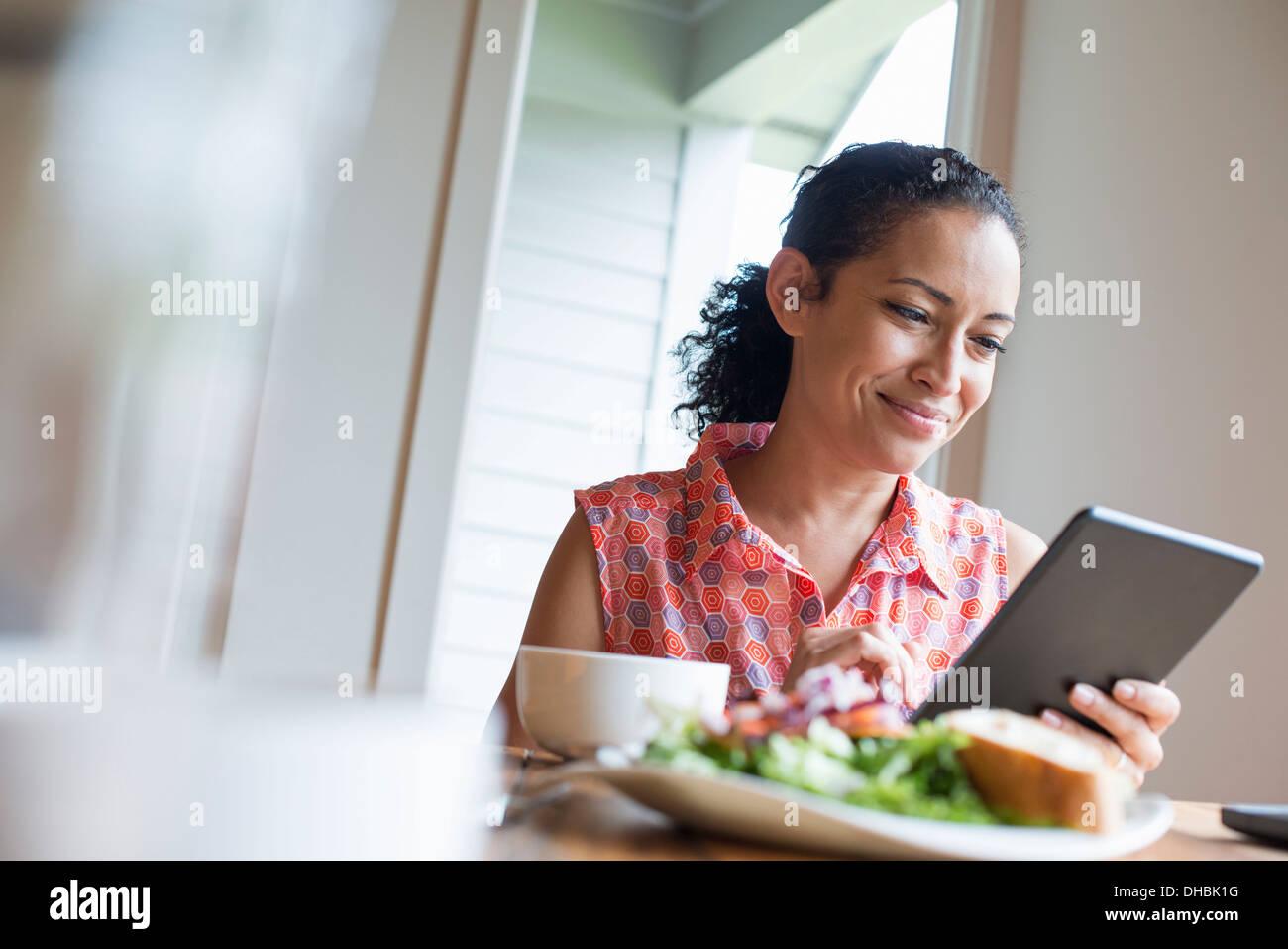 Una mujer joven la lectura de la pantalla de una tableta digital, sentado en una mesa. Café y un sandwich. Imagen De Stock