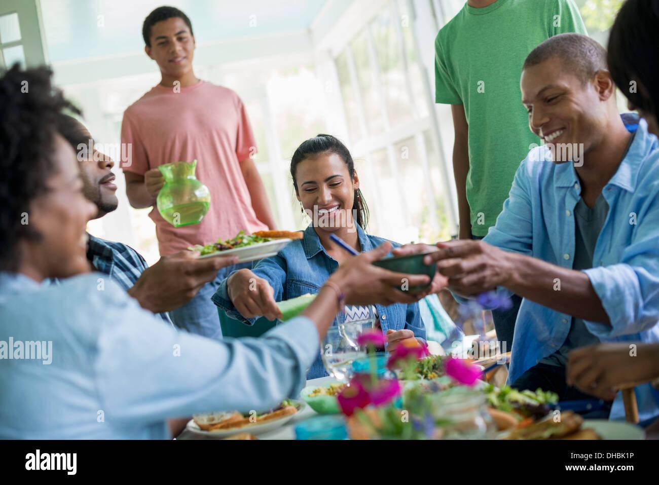 Un grupo de hombres y mujeres alrededor de una mesa compartiendo una comida en una granja de cocina. Imagen De Stock