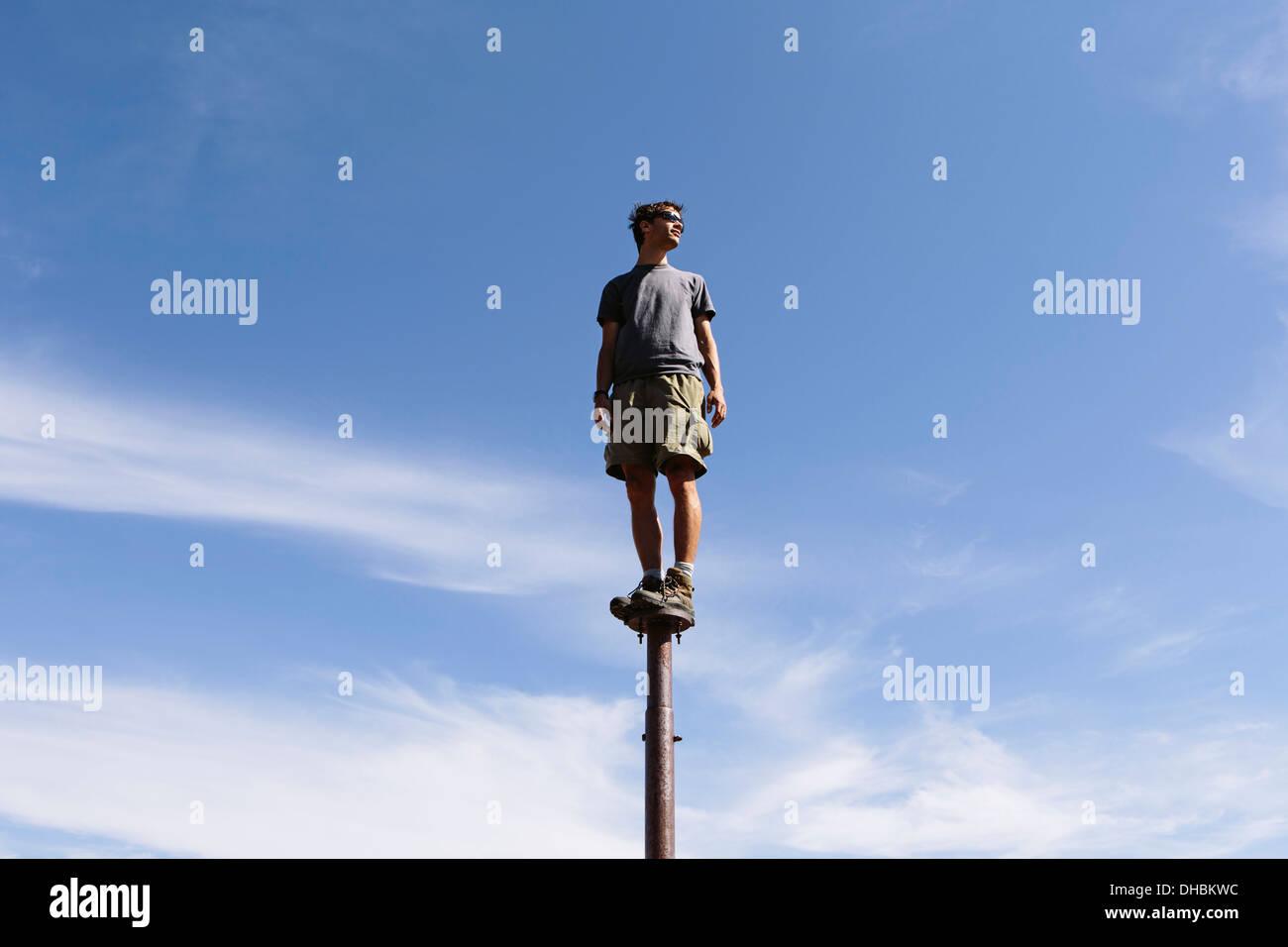 Hombre de equilibrio permanente sobre metal post mirando hacia el inmenso cielo sorpresa lagos alpinos de montaña Imagen De Stock