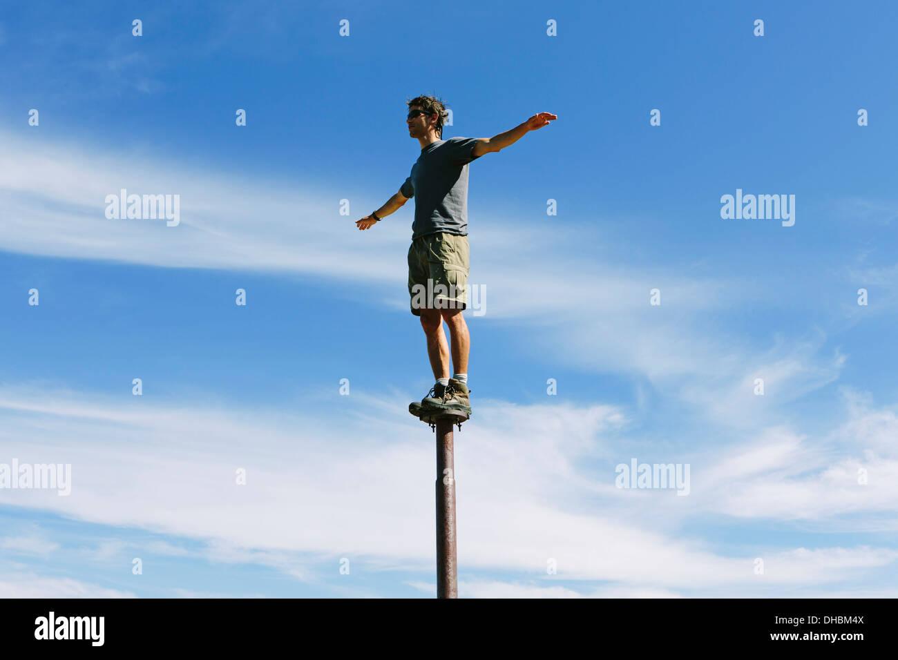 Hombre de equilibrio permanente sobre metal post mirando hacia el inmenso cielo de la sorpresa Mountain Wilderness Imagen De Stock