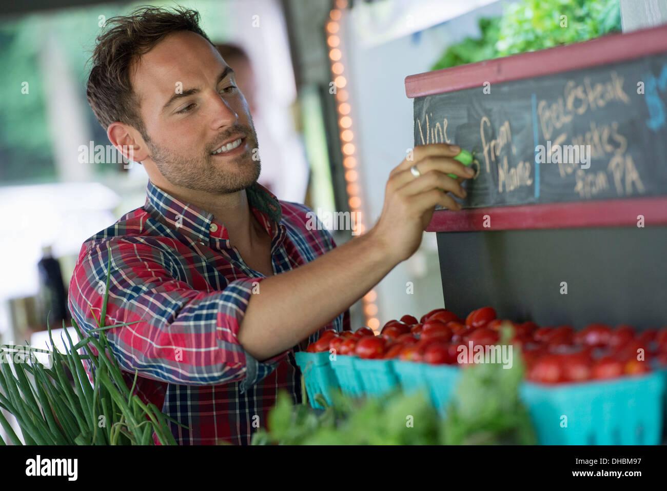 Un stand de frutas orgánicas. Un hombre entizamiento subir los precios en la pizarra. Imagen De Stock