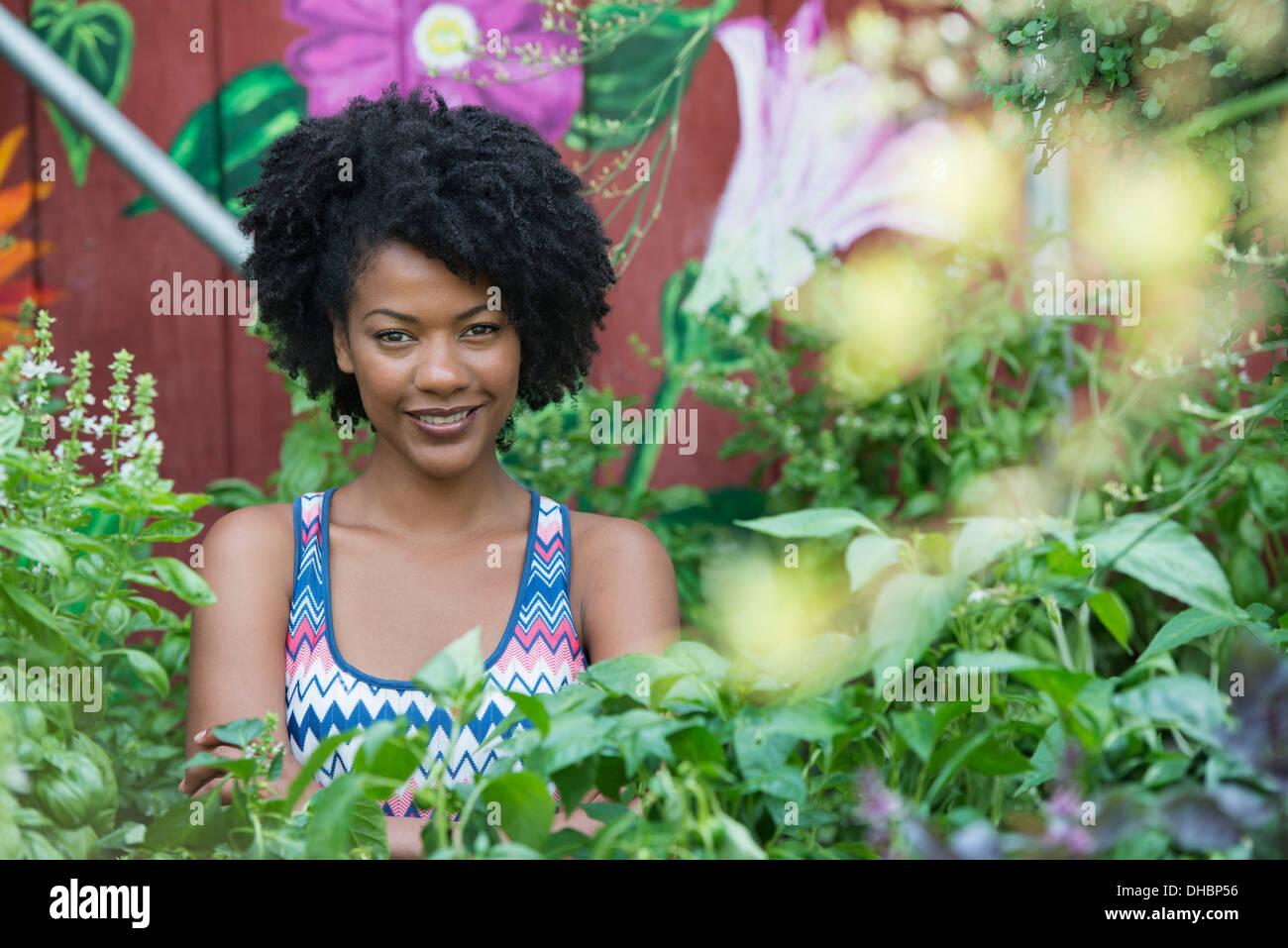 Una mujer de pie en un vivero de plantas, rodeado de plantas, flores y follaje. Imagen De Stock