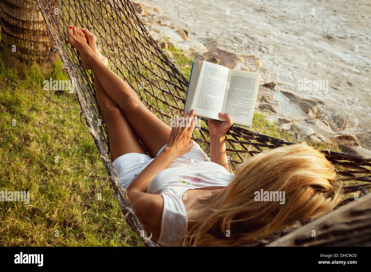 Mujer tumbado en una hamaca en la playa y disfrutar de una lectura del libro Foto de stock