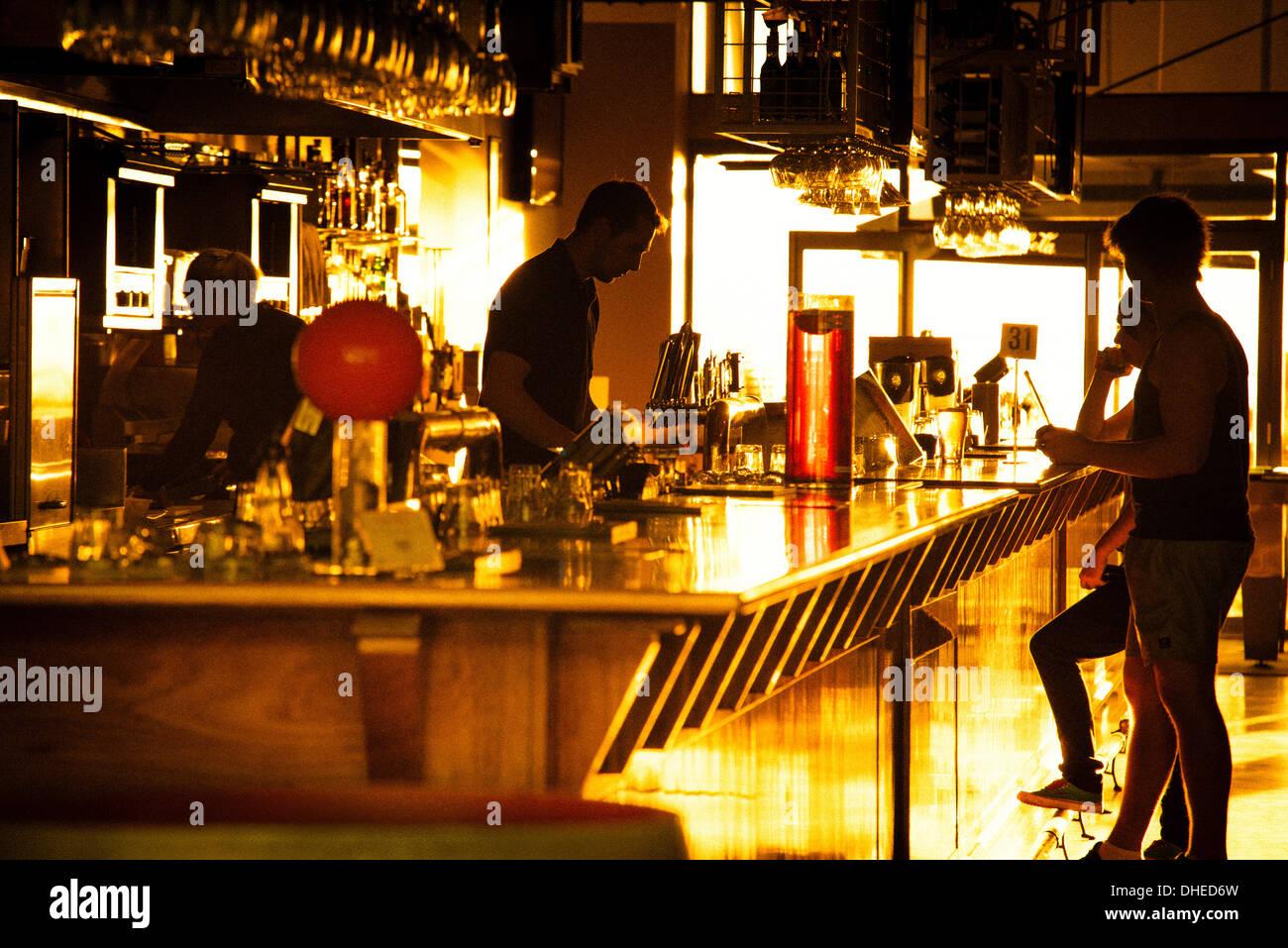 Empleados y patronos de un bar (en Glenelg Adelaida) siluetas contra el atardecer. Imagen De Stock