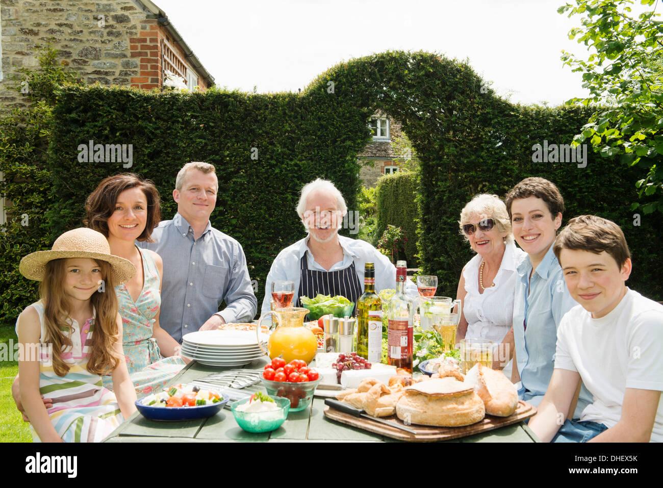 Retrato de familia de tres generaciones de disfrutar de la comida al aire libre Imagen De Stock