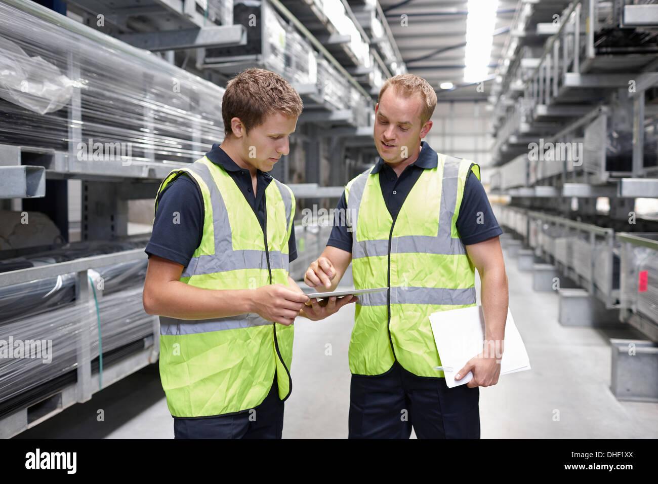 Los trabajadores controlar pedidos en almacén de ingeniería Imagen De Stock