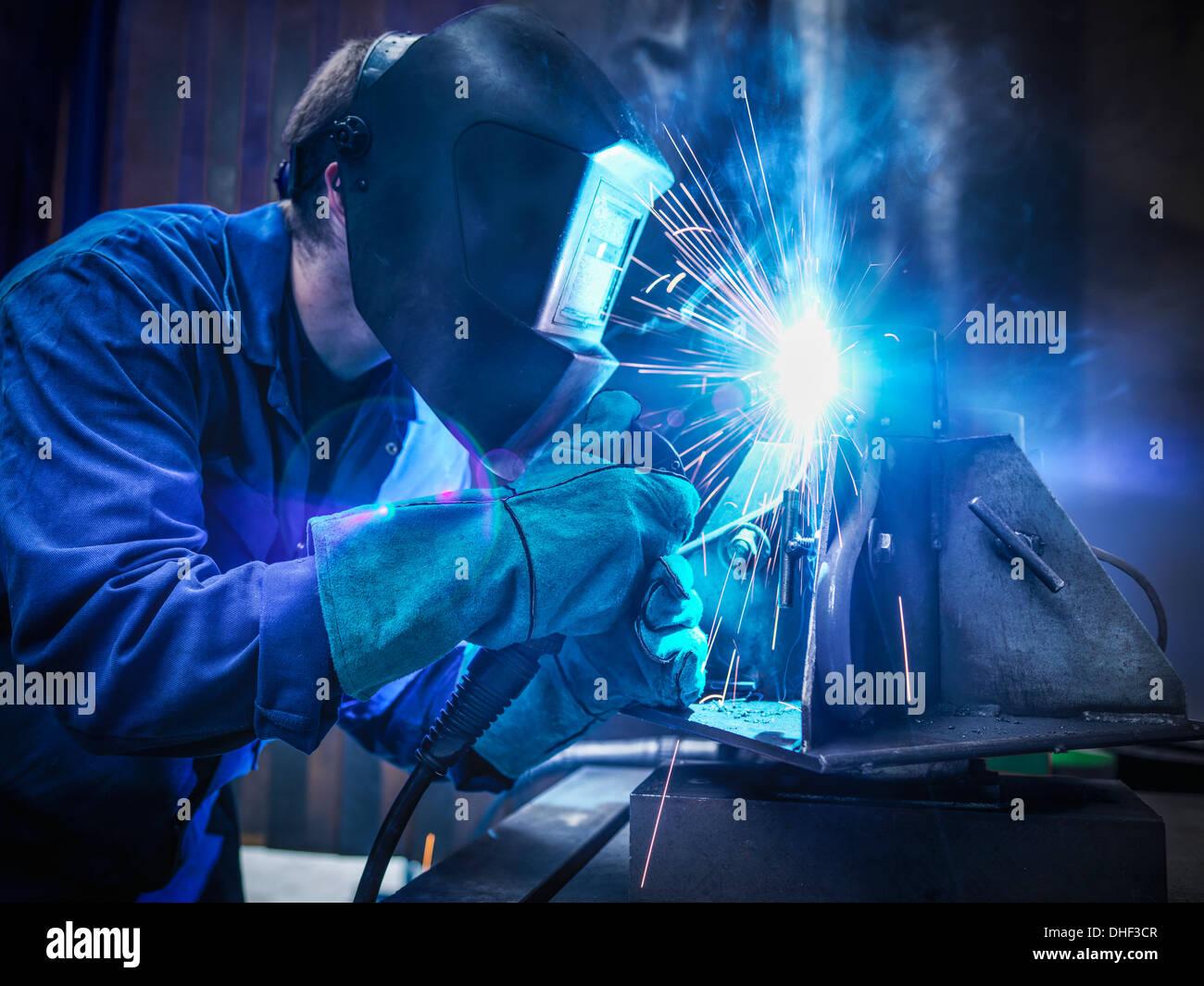 La soldadora Llevar mascarilla y guantes protectores en la fábrica. Imagen De Stock