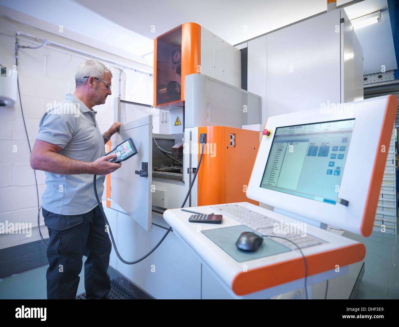 Ingeniero de alambre de funcionamiento Máquina de erosión en la fábrica. Imagen De Stock