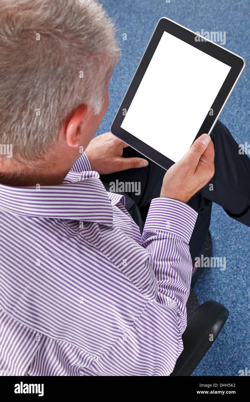 Empresario sentado en una oficina con un equipo tablet PC. Trazado de recorte previsto por la pantalla para agregar Imagen De Stock