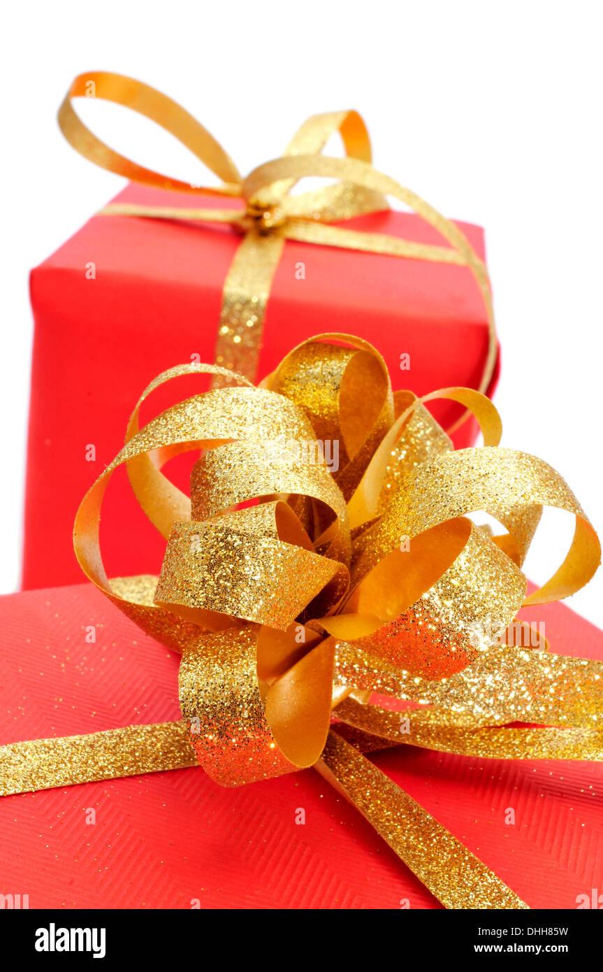 Algunos regalos envueltos con papel de regalo rojo y con una cinta de oro sobre un fondo blanco. Imagen De Stock