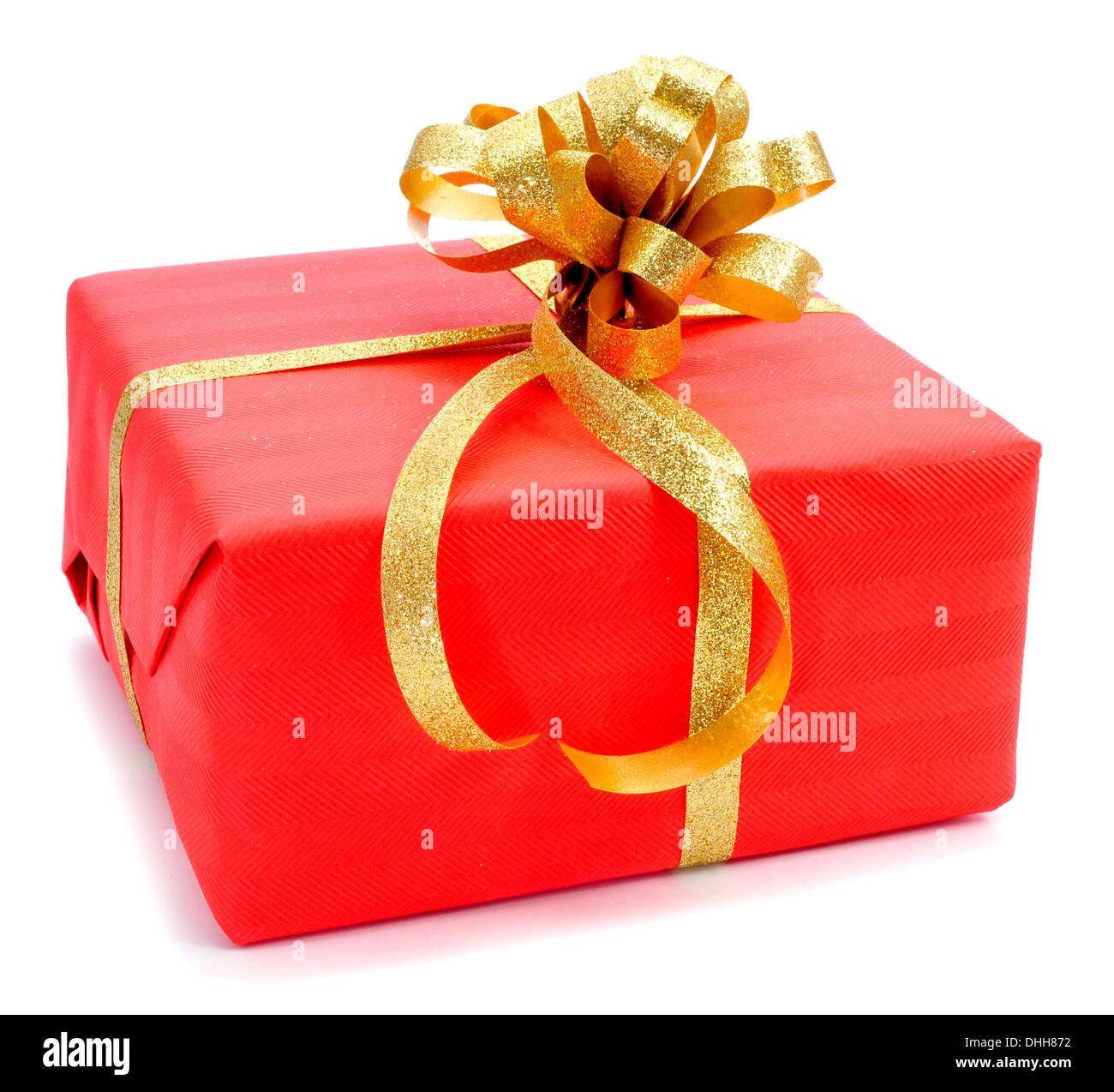 Un regalo envuelto con papel de regalo rojo y con una cinta de oro sobre un fondo blanco. Imagen De Stock