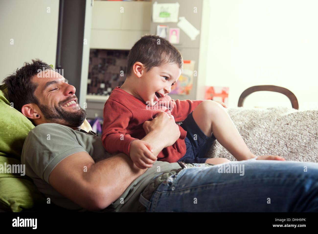 Padre reclinado en el sofá con el hijo en la vuelta Foto de stock