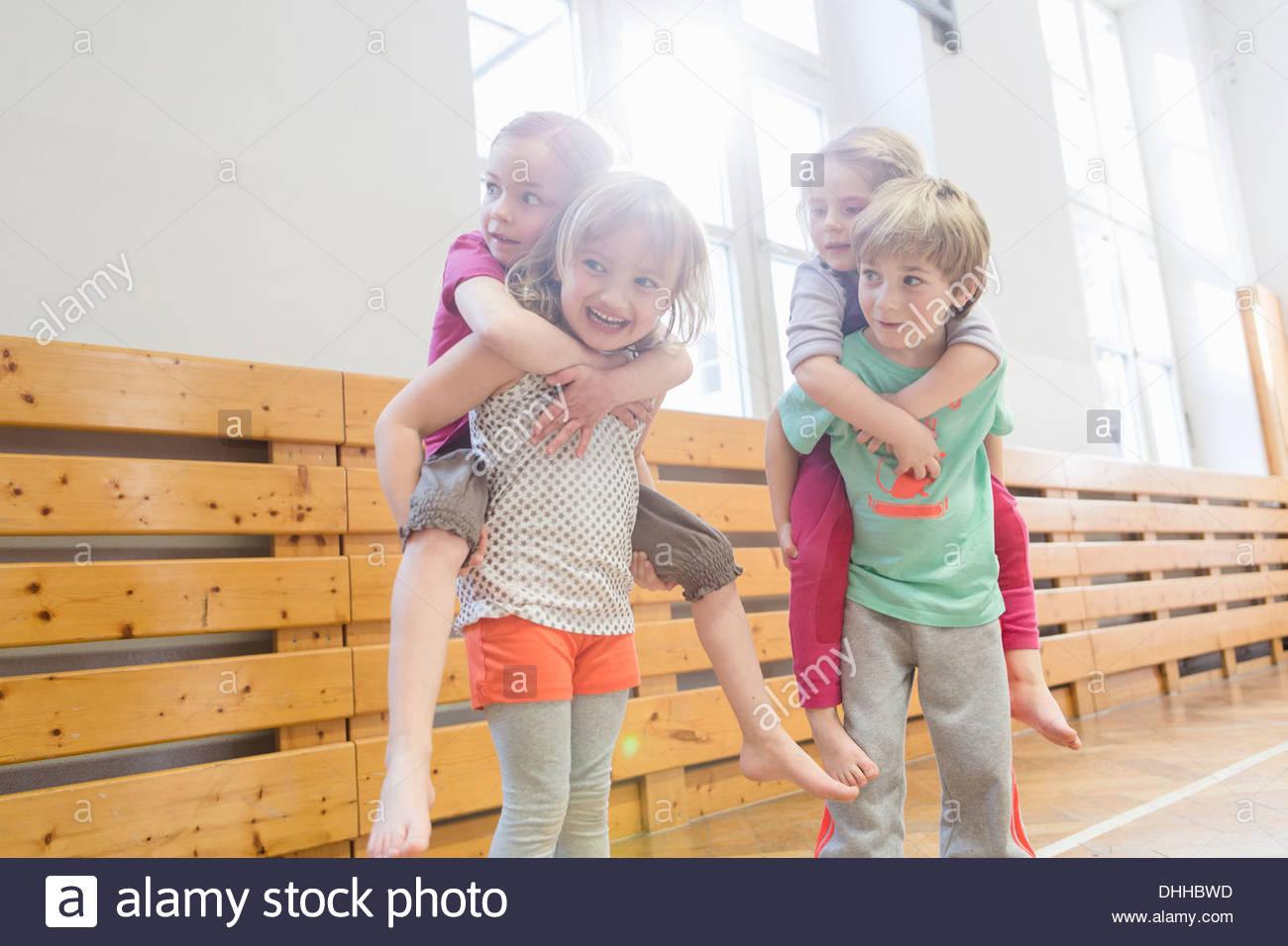 Los niños dando amigos un piggy back Imagen De Stock
