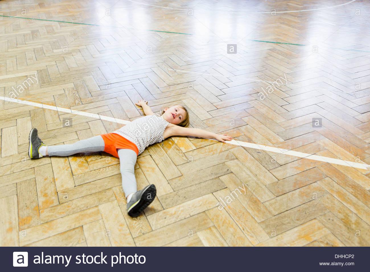 Chica recostada sobre un piso de madera en sala escolar con brazos y piernas separadas Imagen De Stock