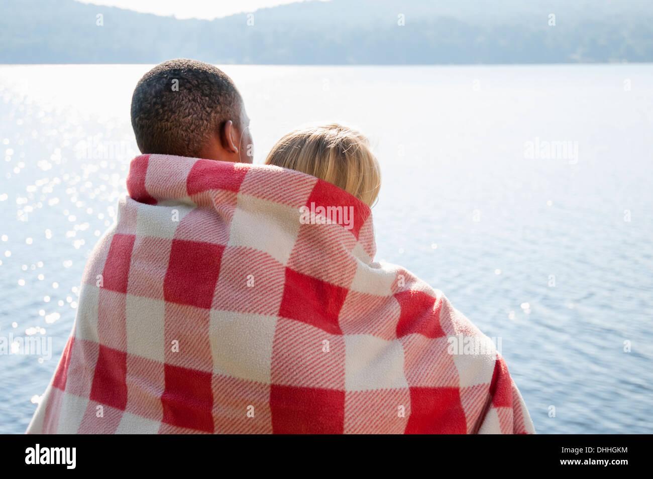 Pareja joven envuelto en una manta por el lago, Hadley, Nueva York, EE.UU. Imagen De Stock