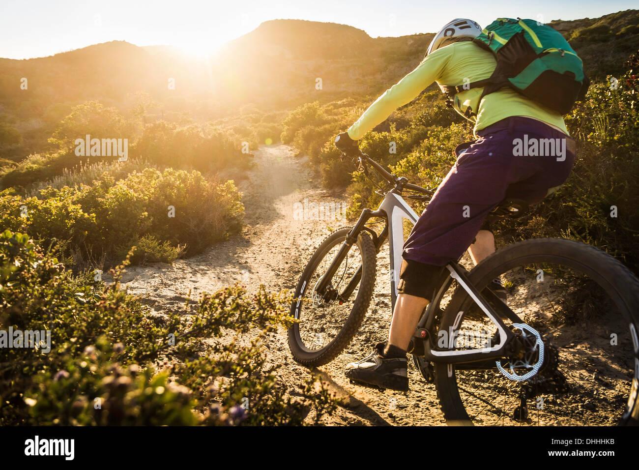Mujer joven el ciclismo de montaña en la pista de tierra, Monterey, California, EE.UU. Imagen De Stock