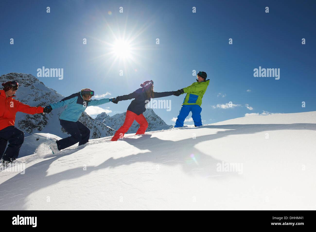 Amigos tirando cada otros cuesta arriba en la nieve, Kuhtai, Austria Imagen De Stock