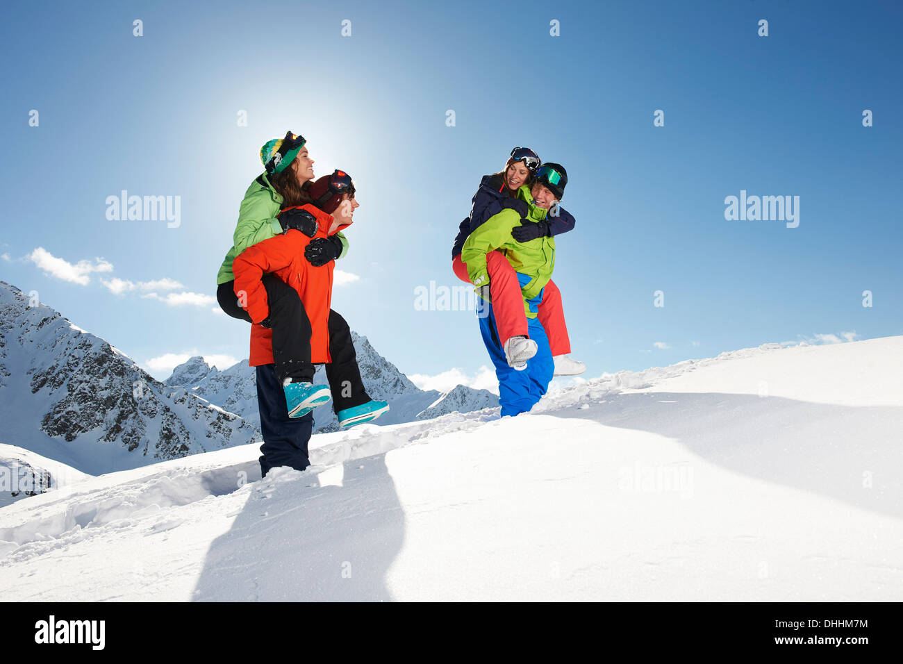 Amigos dando piggy backs en nieve, Kuhtai, Austria Foto de stock