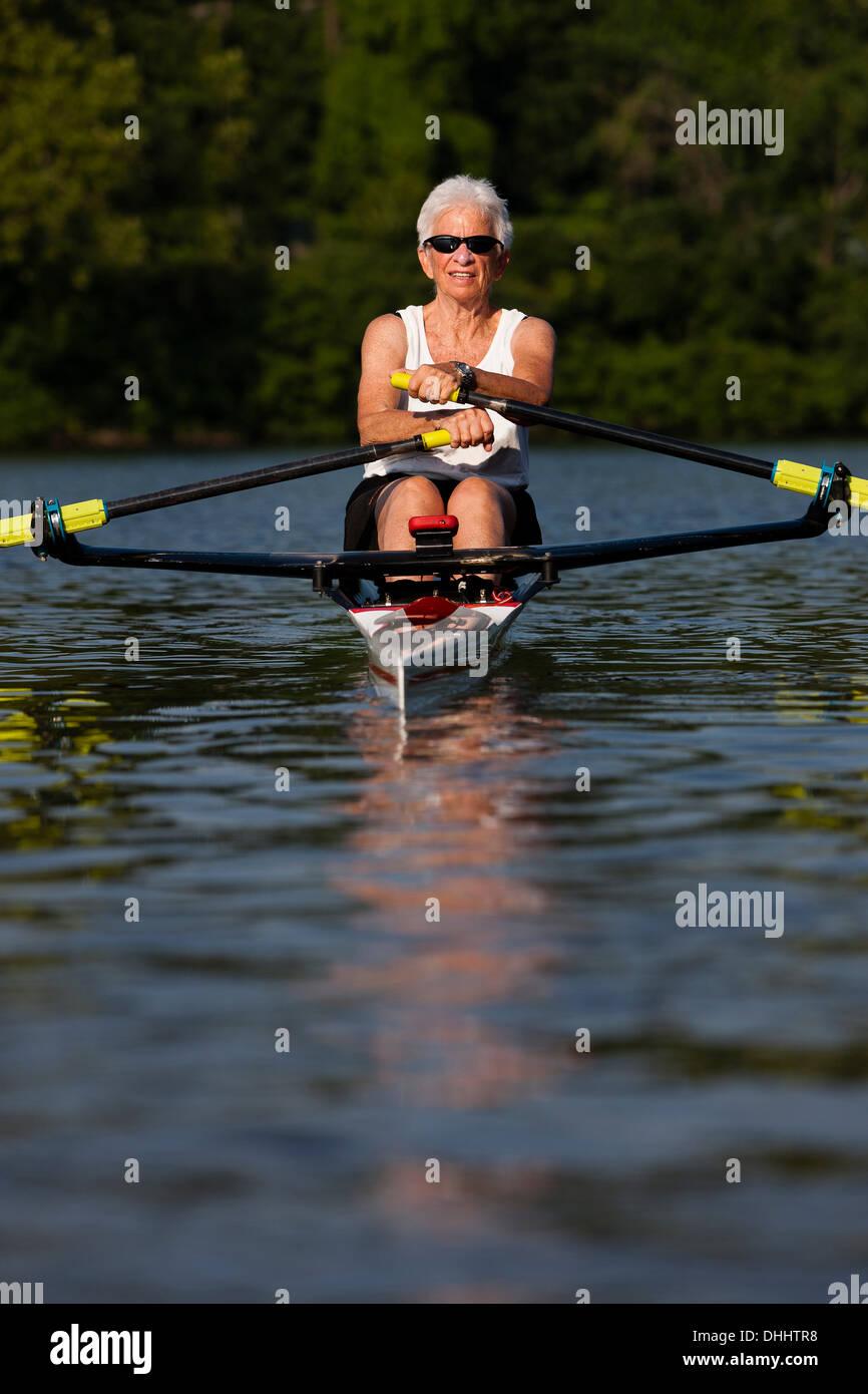 Mujer mayor remando en bote a remo Imagen De Stock