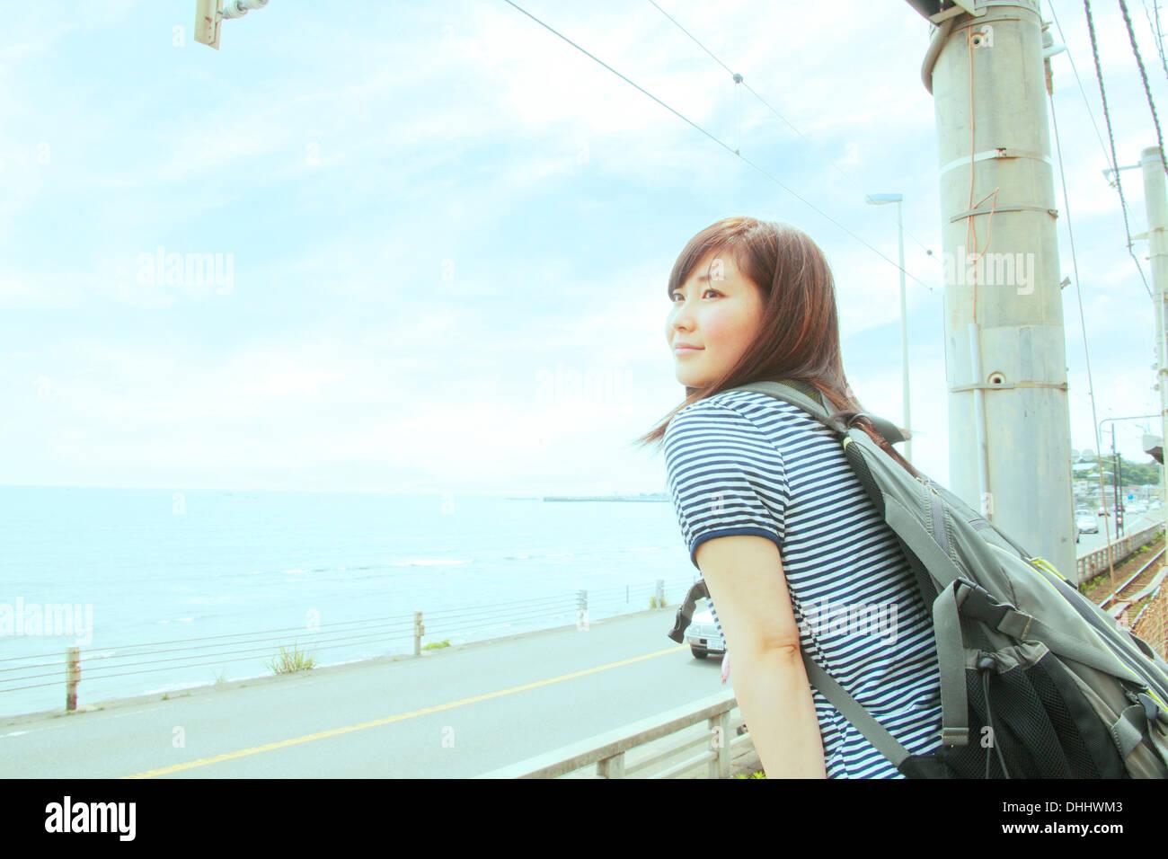 Mujer joven recostada contra la valla, mirando al mar Foto de stock