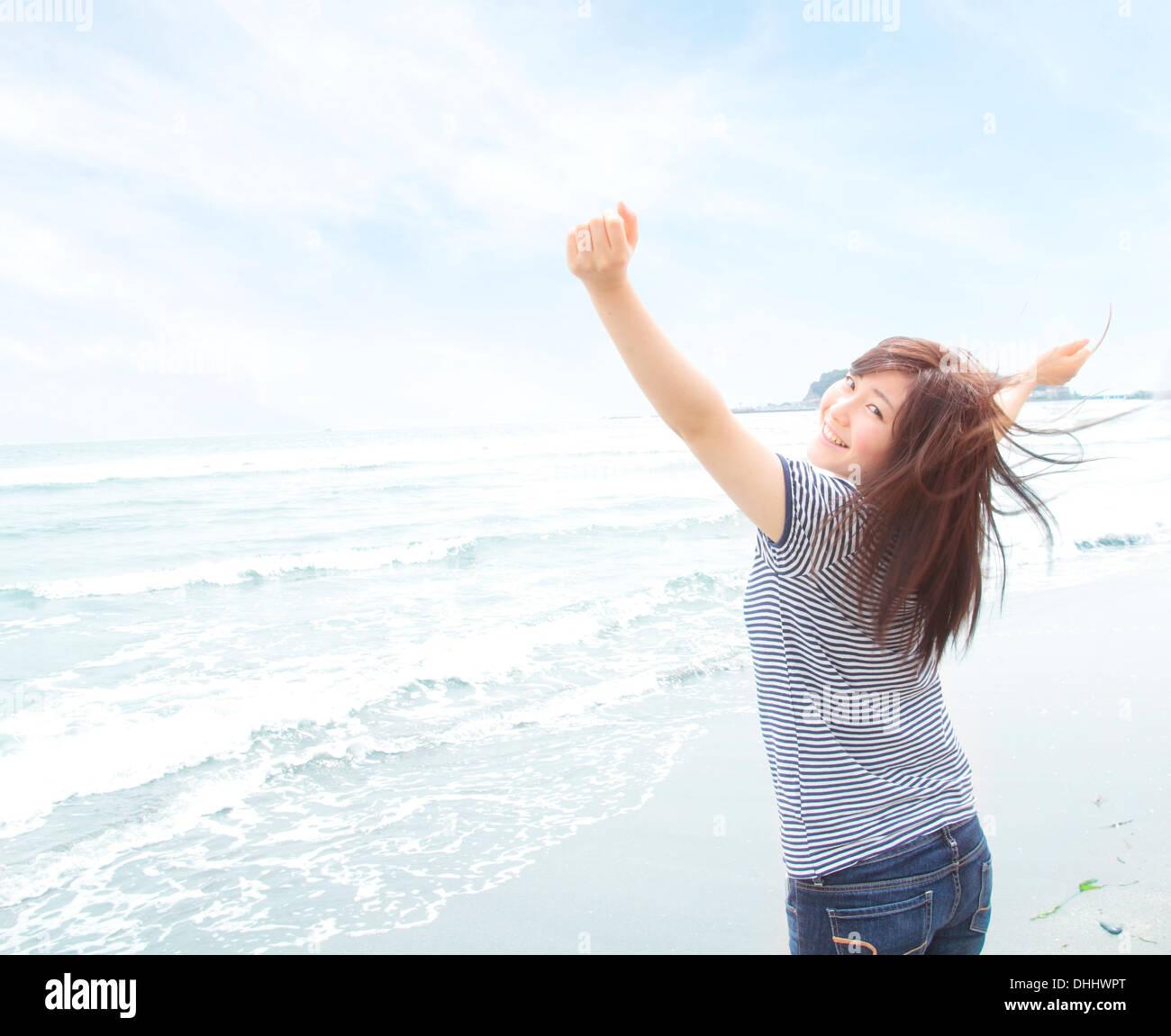 Retrato de mujer joven en la playa con los brazos levantados, mirando por encima del hombro Imagen De Stock