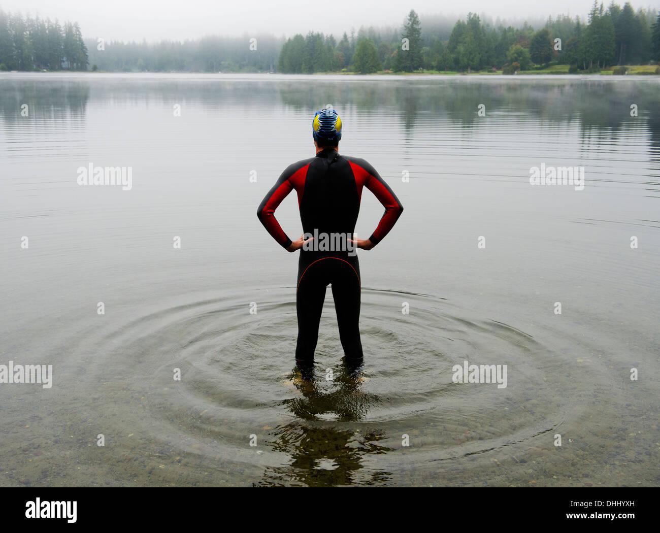 Joven en wet suit preparando para nadar lago Imagen De Stock