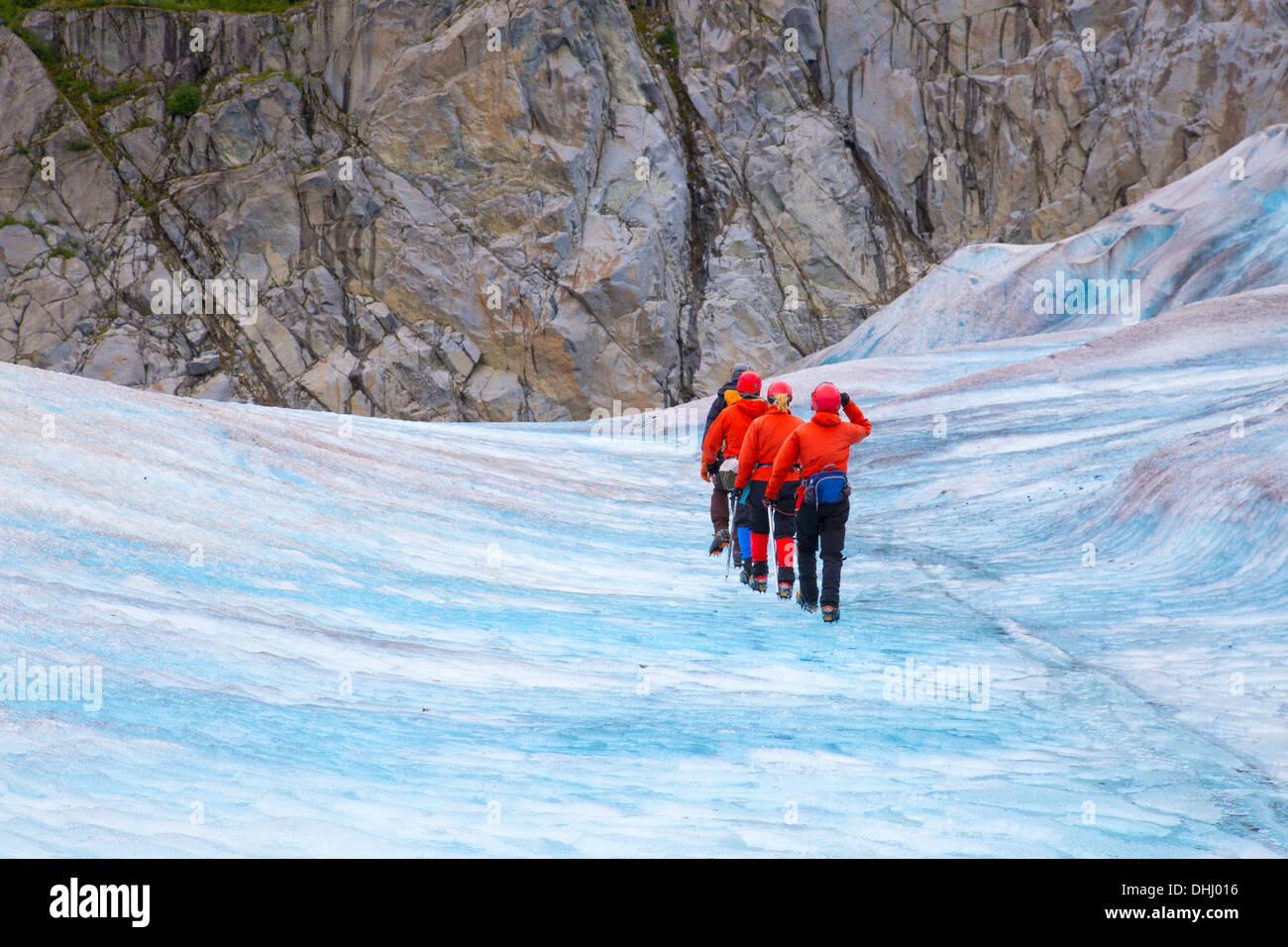 Cuatro personas caminando sobre el glaciar Mendenhall, Alaska, EE.UU. Foto de stock