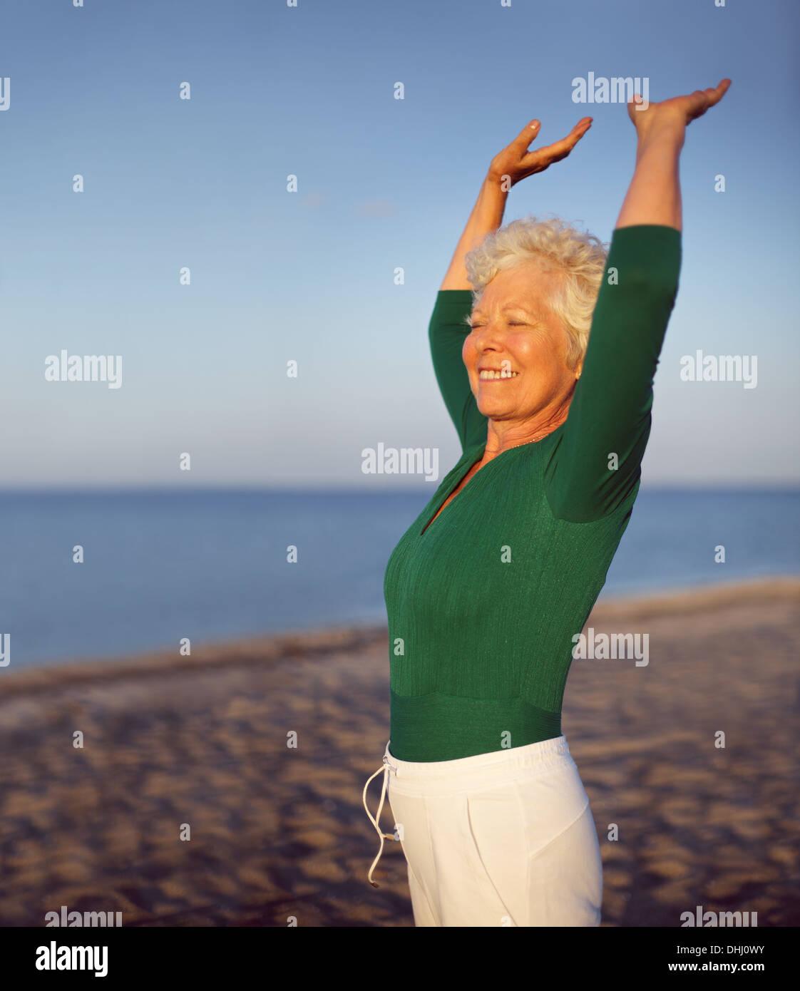 Retrato de hermosa mujer madura practicando yoga en la playa con copyspace. Old mujer caucásica que hacen ejercicio al aire libre para mantenerse en forma. Imagen De Stock