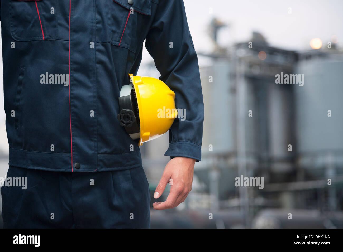 Parte media de joven trabajador sosteniendo un casco amarillo afuera, con fábrica en el fondo Imagen De Stock