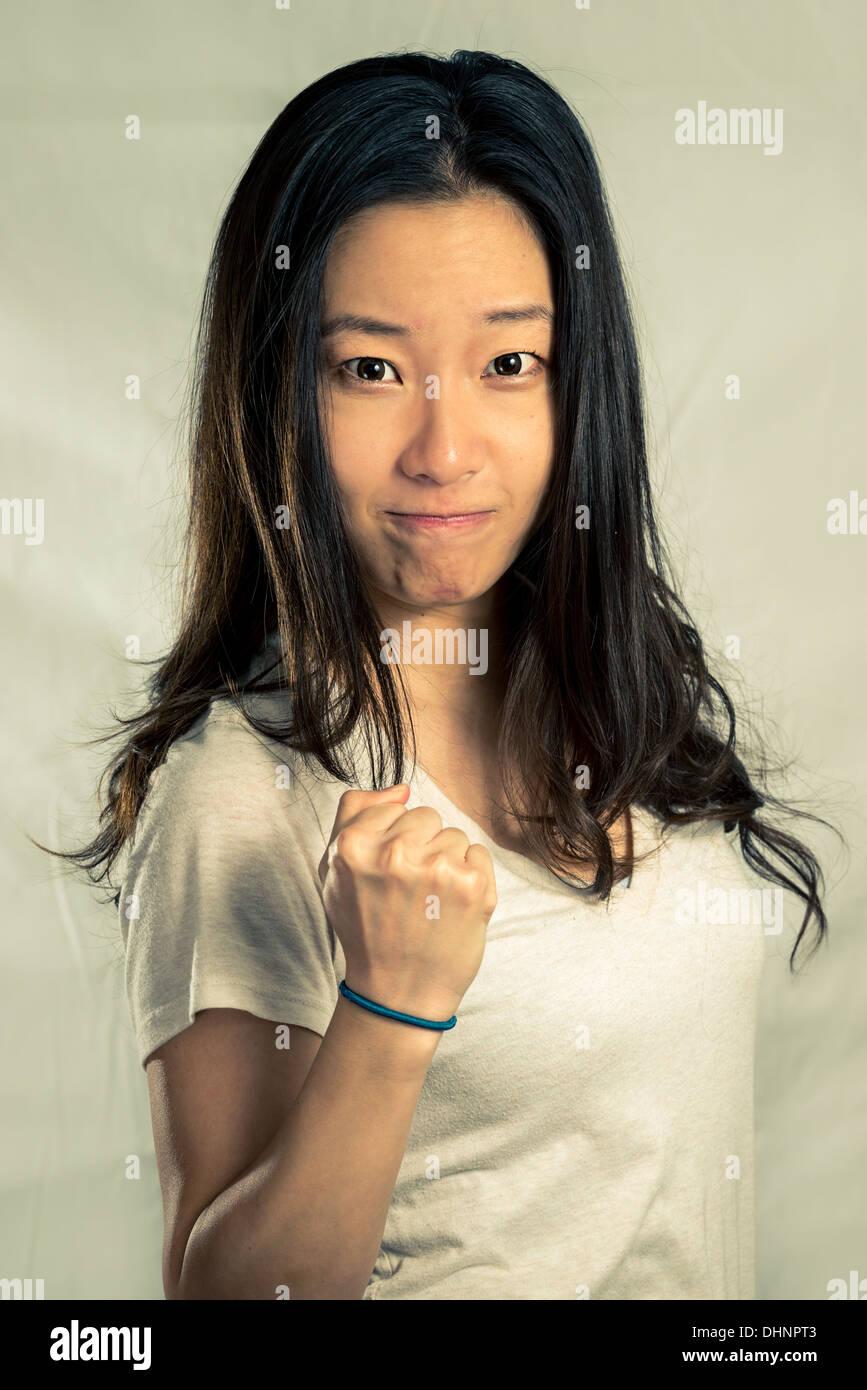 Mujer joven apretamiento su puño para el aliento, con tono de moda y antecedentes Imagen De Stock