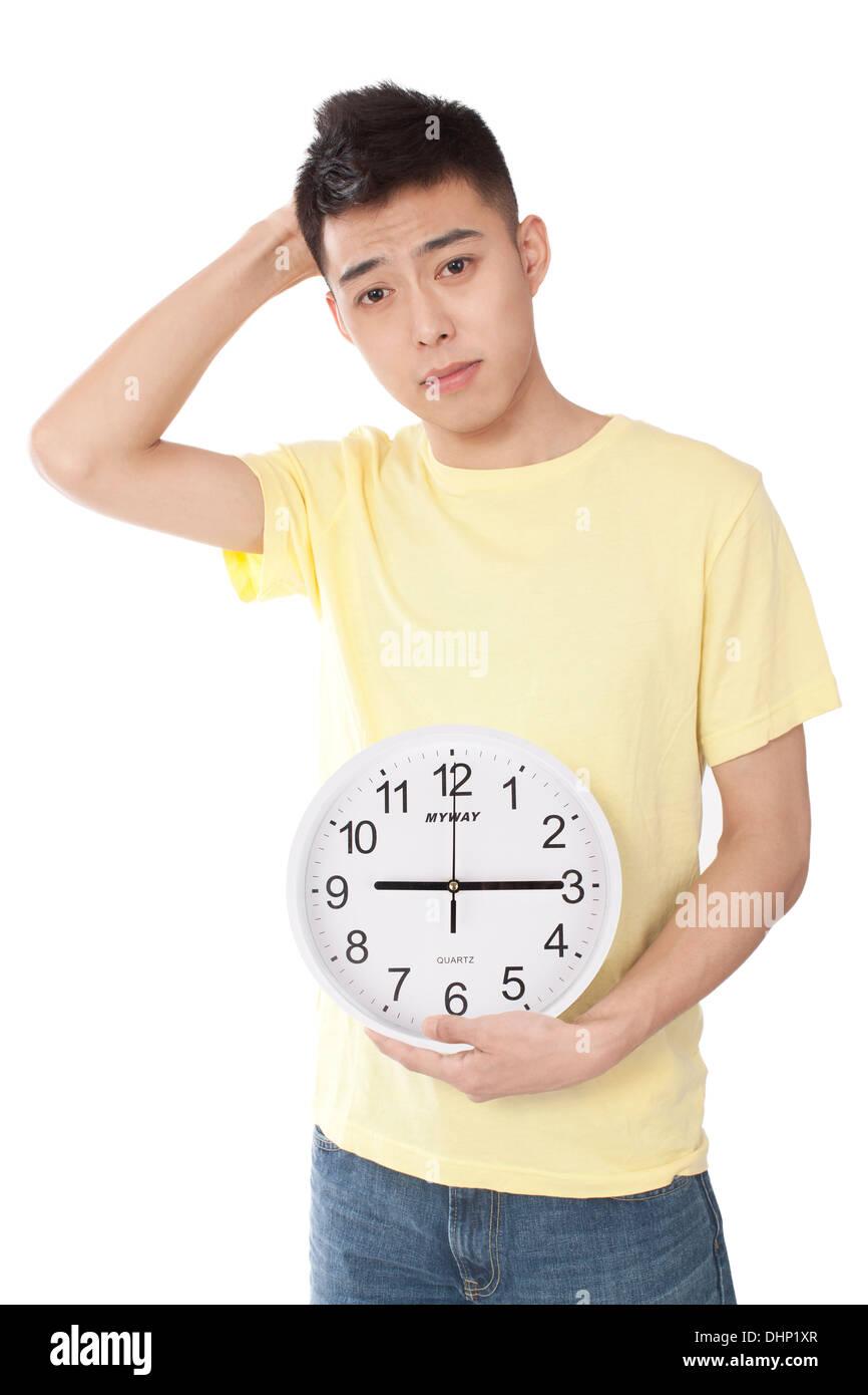 Joven asiática sosteniendo un reloj Foto de stock