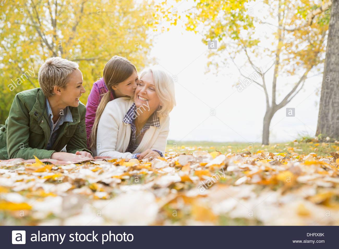 Alegre de generación múltiple femenino acostado en park Imagen De Stock