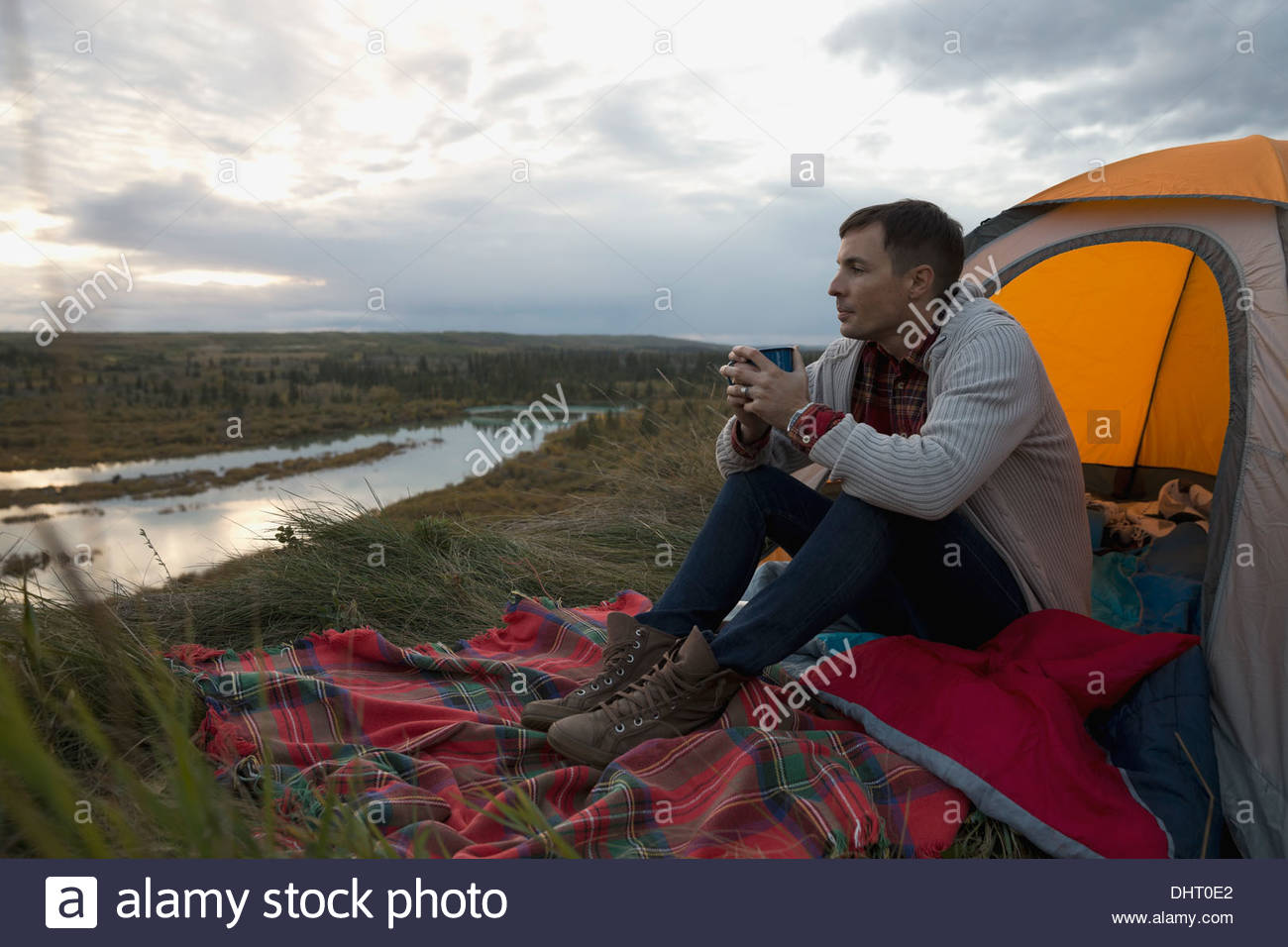 Longitud total del hombre con café en el camping Imagen De Stock