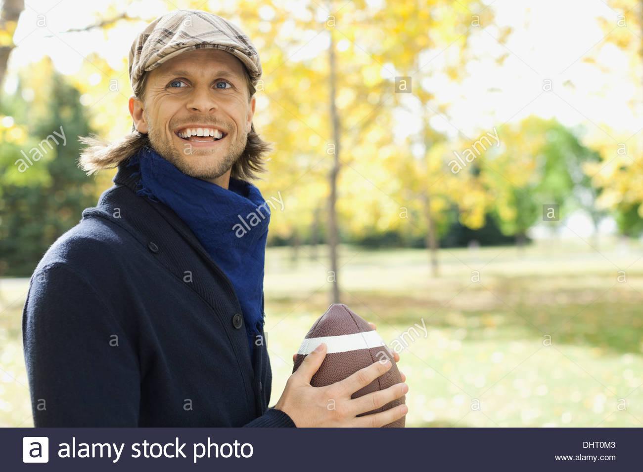 Hombre adulto medio feliz jugando fútbol americano en park Imagen De Stock