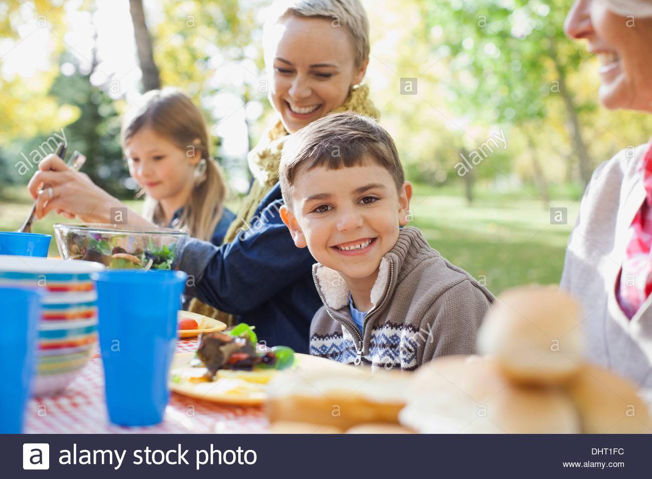 Retrato de muchacho feliz con la familia en la mesa del comedor en park Imagen De Stock