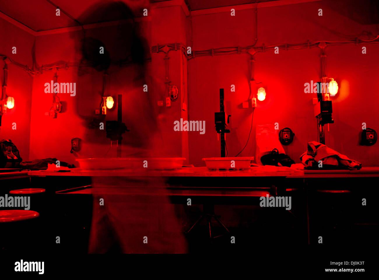 Cuarto oscuro iluminado con luces rojas y gente en movimiento Foto ...