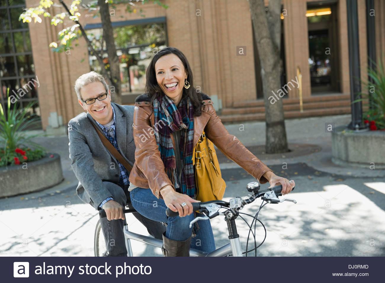Pareja sonriente montando bicicleta tándem Imagen De Stock