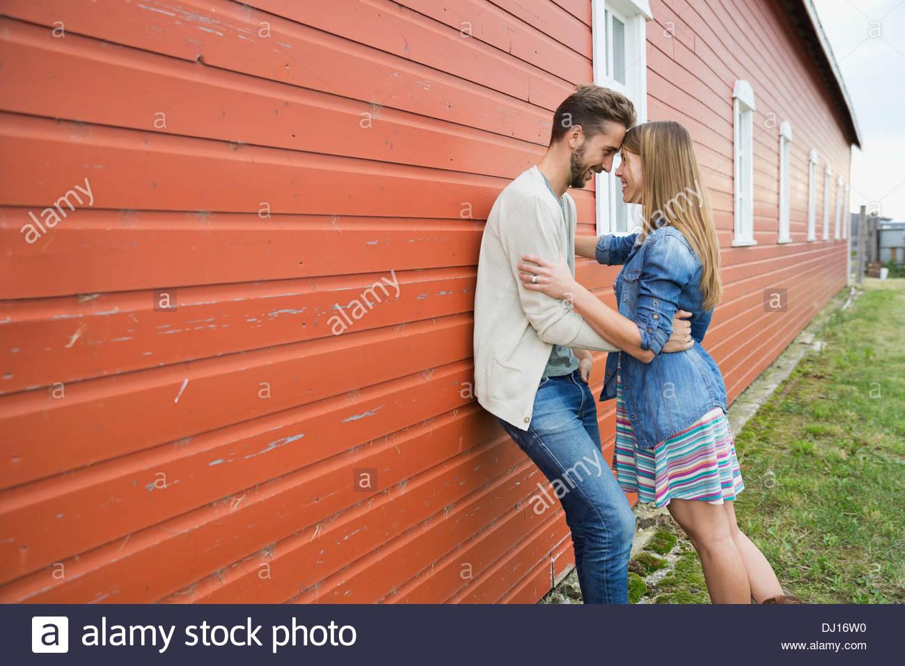 Vista lateral de la pareja romántica de pie contra el granero Imagen De Stock