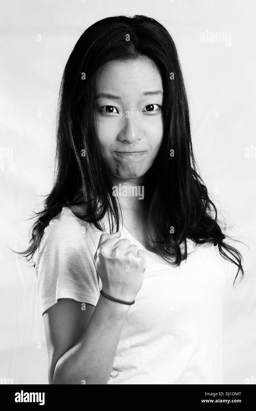 Retrato de mujer joven atractiva apretamiento su puño de aliento, de estilo en blanco y negro Imagen De Stock