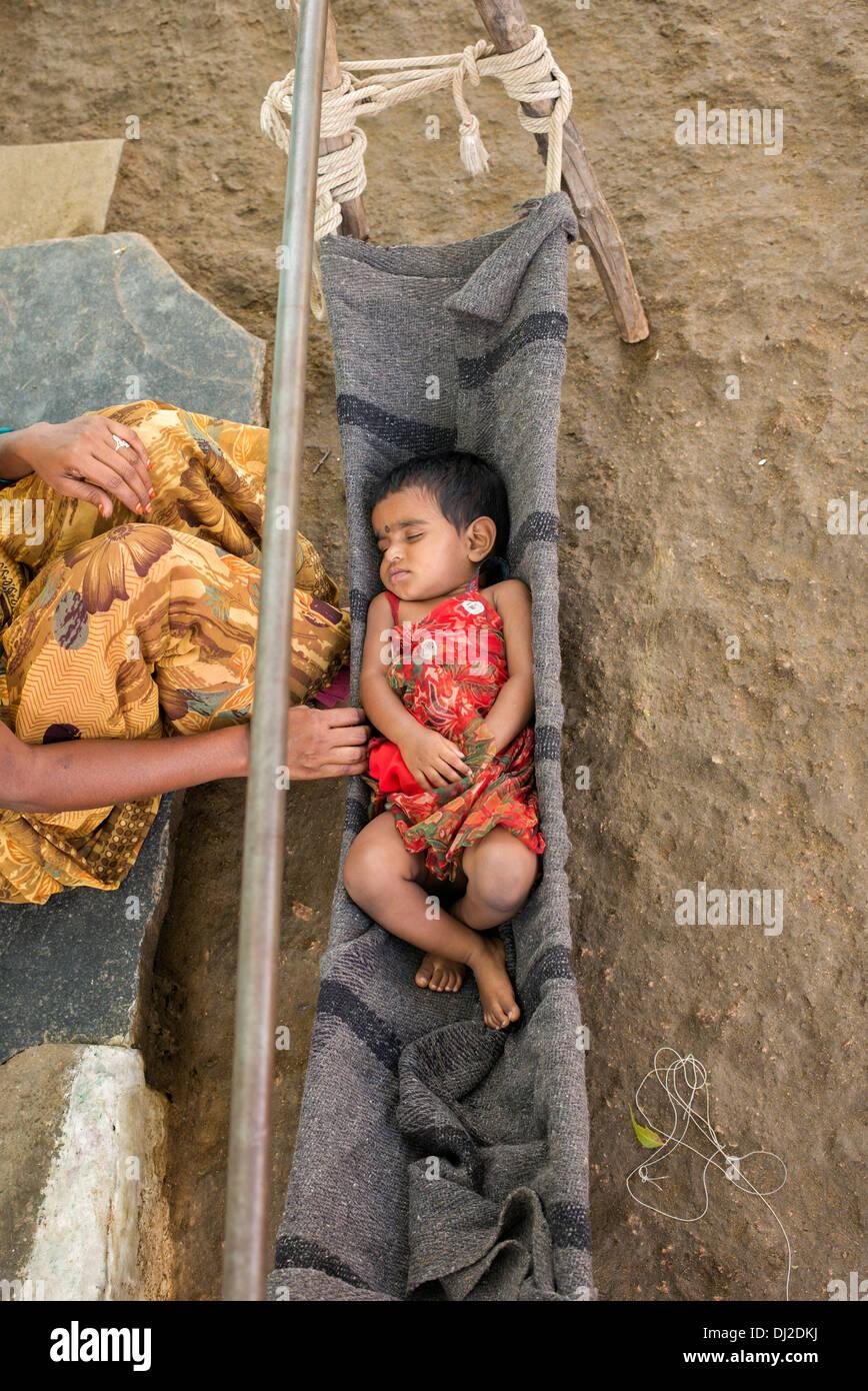 Indian baby girl dormir en una cuna de fabricación casera en una aldea india. En Andhra Pradesh, India Imagen De Stock