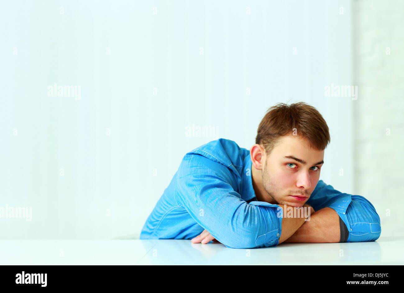Pensativo joven empresario poniendo sobre la mesa y mirando a la cámara Imagen De Stock