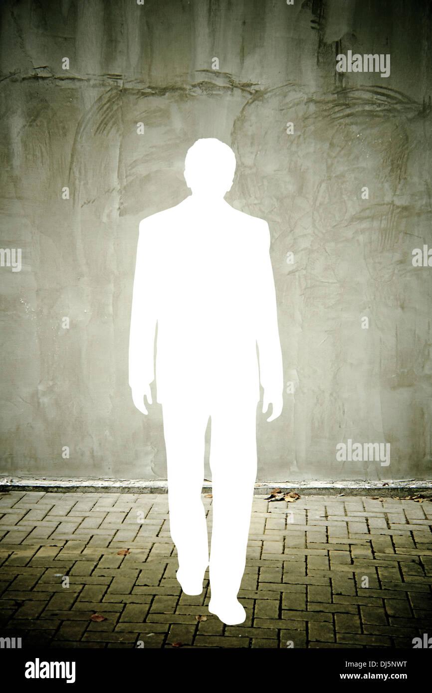 Recorte la silueta de un hombre de negocios en una pared gris angustiado Imagen De Stock