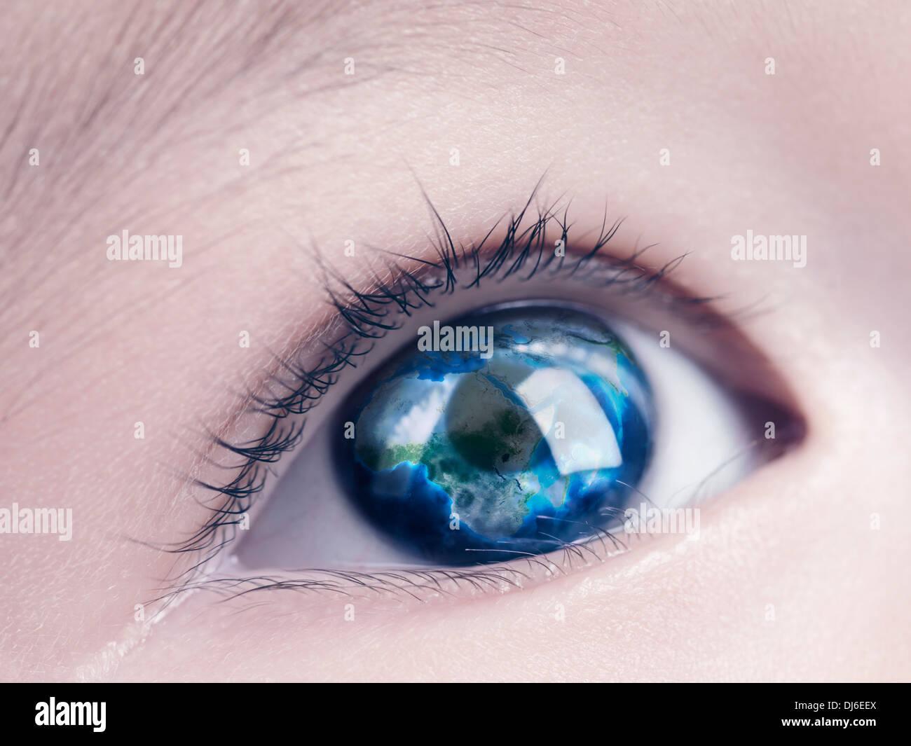 Primer plano de un ojo azul del niño con el globo terrestre, mapa del mundo reflejando en ella Imagen De Stock