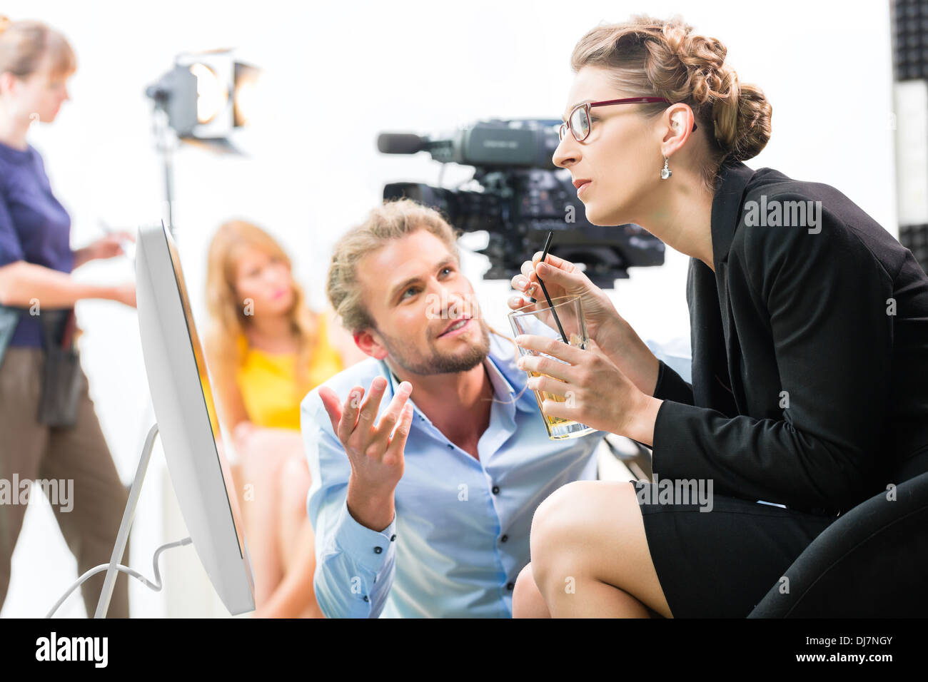 Equipo o Director discutiendo durante un descanso de la dirección de escena en el set de una producción de vídeo comercial o reportaje en una pantalla Imagen De Stock
