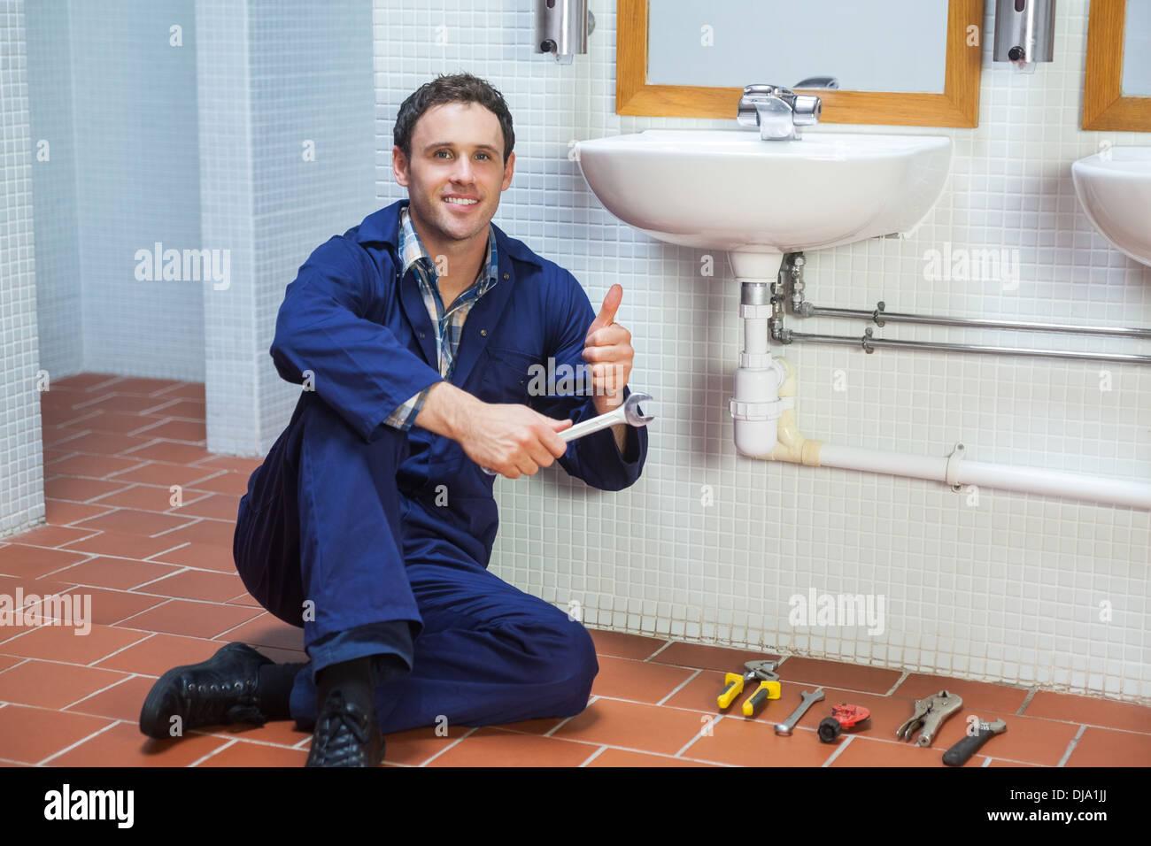 Guapo fontanero feliz sentado junto al fregadero mostrando pulgar arriba Imagen De Stock