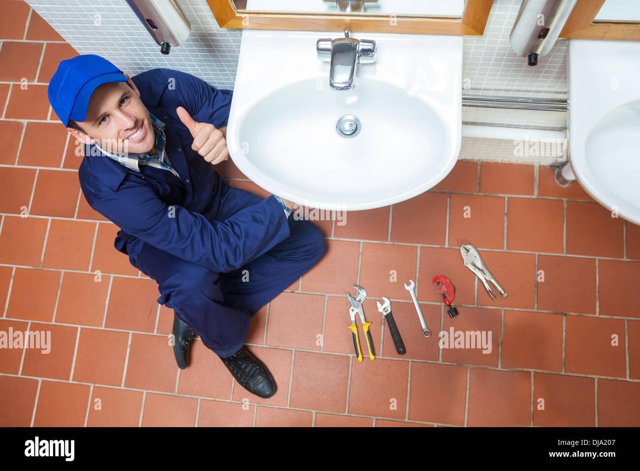 Alegre fontanero reparando sink mostrando pulgar arriba Imagen De Stock