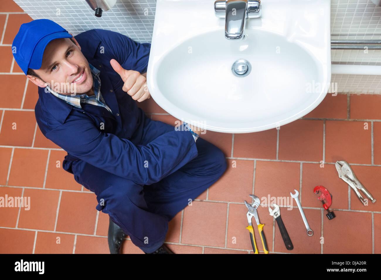Fontanero sonriente reparación sink mostrando pulgar arriba Imagen De Stock